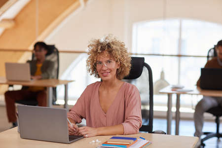 Portrait of mature businesswoman with curly hair sitting at her workplace with laptop and smiling at camera with her colleagues in the background Stock Photo