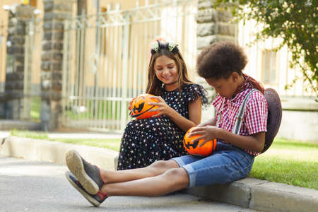 Children sitting on the ground outdoors they getting treats during Halloween holiday