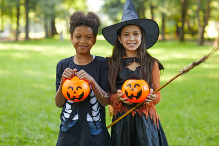 Portrait of two happy friends smiling at camera during Halloween party in the park outdoors Standard-Bild