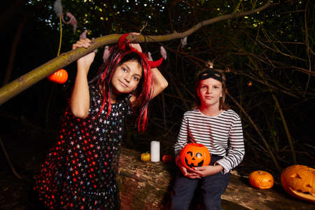 Portrait of two girls looking at camera while sitting outdoors in the dark during Halloween party Standard-Bild