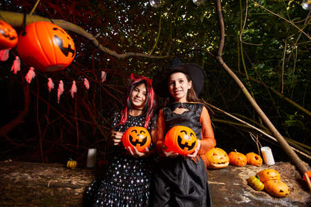 Portrait of two girls in costumes holding toy pumpkins and smiling at camera they are at the party in the dark Standard-Bild