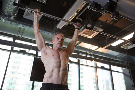 Muscular mature man pulling up on horizontal bar in the gym