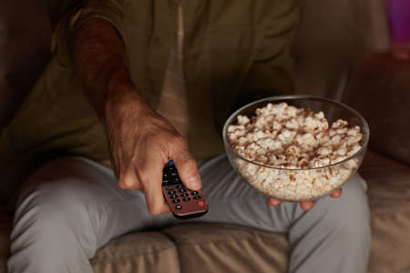 Close-up of man changing channels on TV while watching TV and eating popcorn