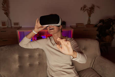 Young woman sitting on sofa in virtual glasses playing in virtual game at home