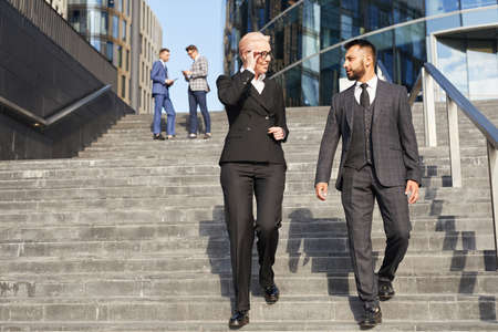 Mature businesswoman talking to businessman while they moving down the stairs outdoors