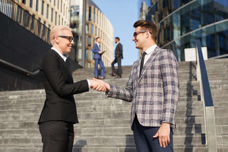 Mature businesswoman in suit shaking hands with young businessman while they standing on stairs in the city