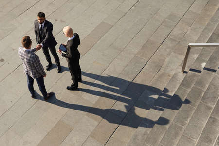 High angle view of business partners shaking hands they meeting outdoors near the stairs of office building