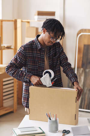 African man closing box with adhesive tape he preparing parcels for delivery