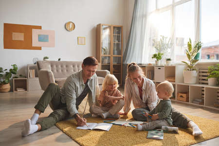 Two parents drawing on the floor together with their two children in the living room