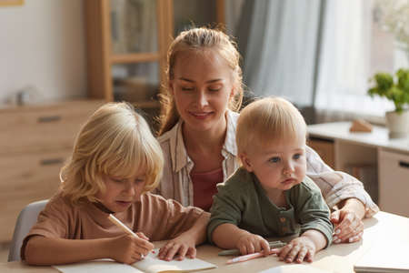 Young mother sitting at the table with baby and helping to her elder son with homework