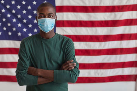 Portrait of Afro-American man in protective mask standing with his arms crossed and looking at camera against the American flag