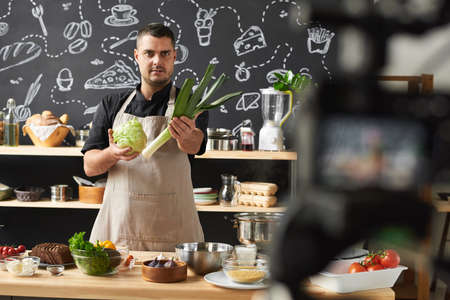Portrait of professional chef holding fresh vegetables and telling about them to the camera for his blog