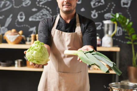 Close-up of cook in apron showing the fresh vegetables in his hands standing in the kitchen 免版税图像