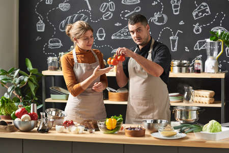 Young couple in aprons examining fresh tomatoes while standing near the table and preparing food in team in the kitchen
