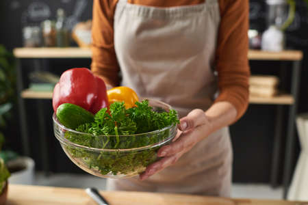 Close-up of woman in apron holding bowl with fresh vegetables she is going to cook salad 免版税图像
