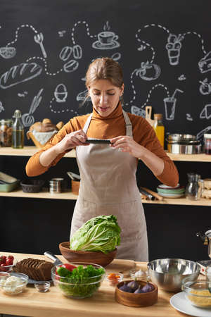 Young woman in apron making photo of fresh vegetables in bowl on her mobile phone standing in the kitchen 免版税图像 - 157973383
