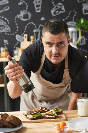 Portrait of mature man in apron looking at camera while adding pepper on sandwiches on the table 免版税图像