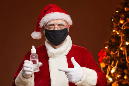 Portrait of Santa Claus in red costume wearing protective mask pointing at antiseptic in his hand standing at studio