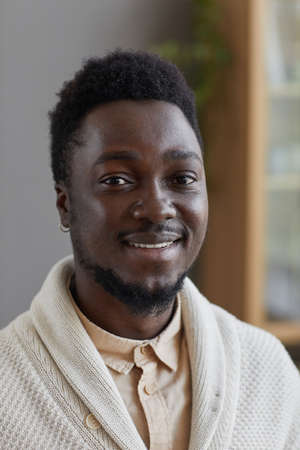 Portrait of African young man in white sweater smiling at camera