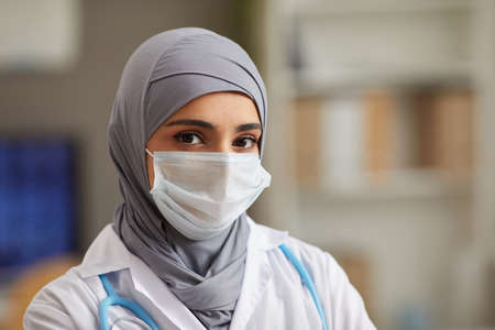 Close-up of muslim female doctor in protective mask looking at camera working at hospital Foto de archivo