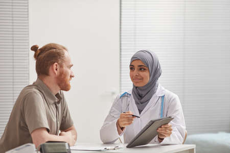 Female doctor in hijab using digital tablet while discussing methods of treatment with her patient at the table at hospital