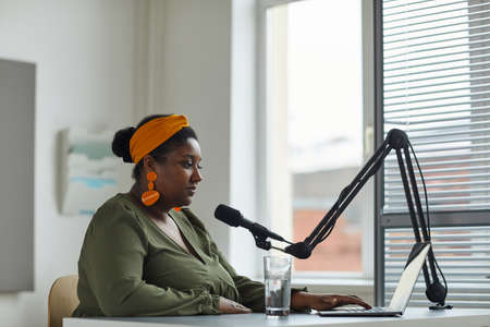 African radio host sitting at the table in front of laptop and speaking on microphone working on radio