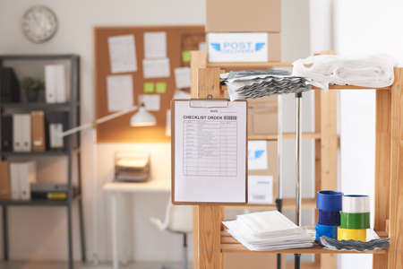 Image of checklist order on the clipboard hanging on the glass wall at modern office
