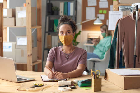 Portrait of young tailor in protective mask looking at camera while working at her workplace in workshop