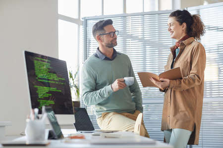 Mobile apps developers discussing work together standing near the table with computer at office