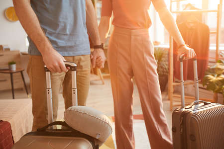 Close-up of young couple standing with luggages in the room they are going to travel 免版税图像