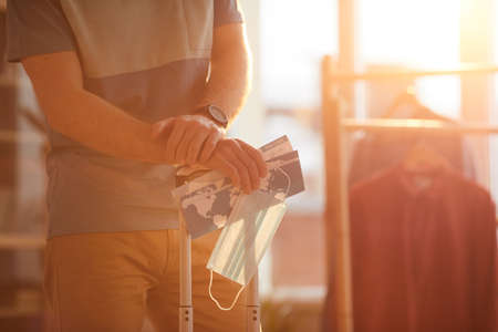 Close-up of man standing with luggage and tickets and waiting for his flight he going in business trip 免版税图像