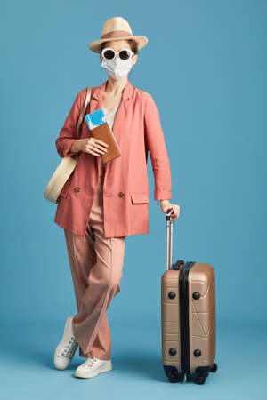 Portrait of young traveler in mask and in sunglasses standing with luggage against the blue background