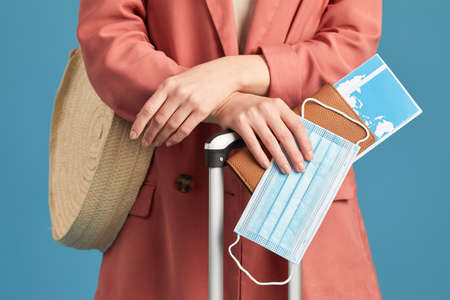 Close-up of tourist with passport and airplane tickets standing against the blue background