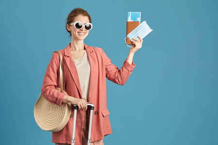 Portrait of happy woman in sunglasses with tickets and passport smiling at camera standing against the blue background