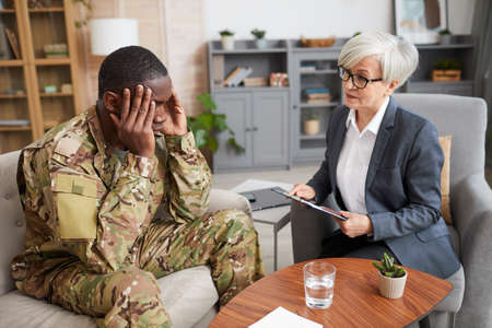 Depressed military man sitting on sofa holding his head with hands and talking to psychologist during meeting 免版税图像
