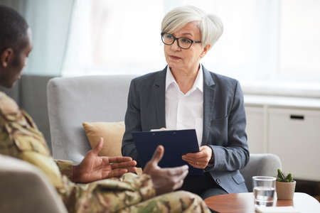 Psychotherapist in eyeglasses talking to military man during their therapy session at office 免版税图像