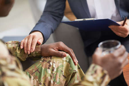 Close-up of military man drinking water and talking to psychotherapist at meeting