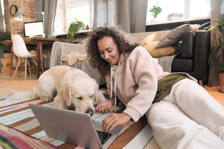 Young woman lying on the floor with her dog and using laptop computer in the living room