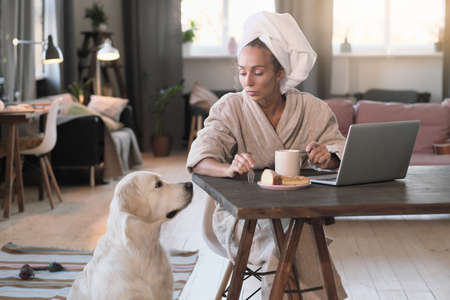Young woman in bathrobe having breakfast at her workplace and talking to her dog in the room
