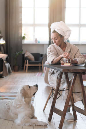 Young woman in bathrobe sitting at the table and drinking coffee during her conversation with her dog in the room
