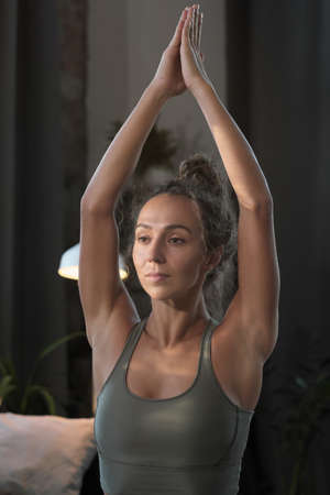 Young healthy woman in tank top stretching her arms during sports training at home