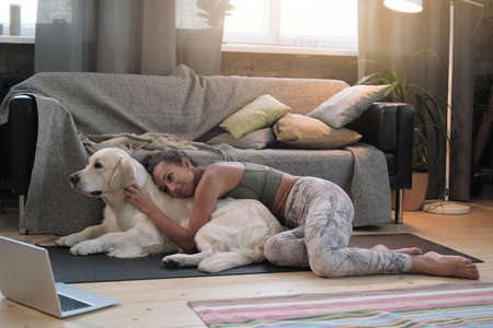 Young woman lying on the floor in the room together with her dog and watching movie online on laptop