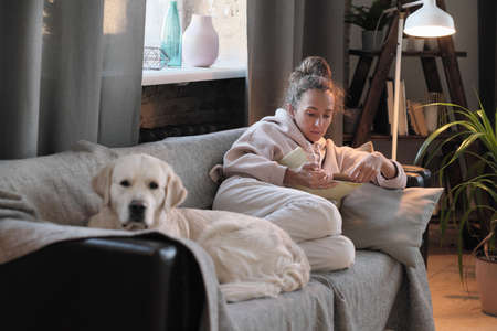 Young woman sitting on sofa with her dog and reading a book during her leisure time at home