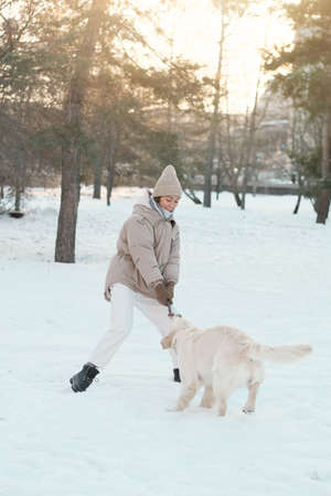 Young woman in warm clothing walking outside together with her dog