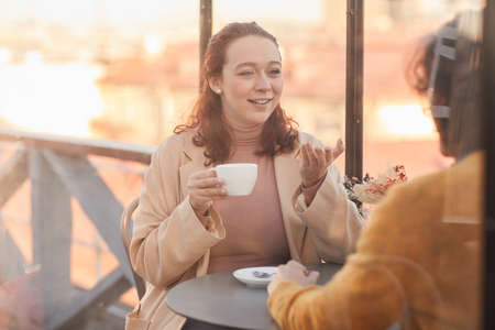 Young woman drinking coffee and talking to her friend during their meeting in cafe