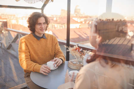 Young couple sitting at the table with cups of tea and talking to each other during their meeting in cafe
