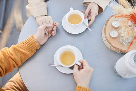 Close-up of young couple holding hands and drinking tea during their romantic date at the restaurant