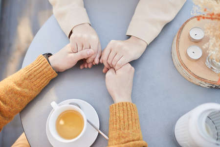 High angle view of loving couple holding each other for hands while drinking tea at the table