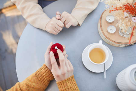 Close-up of man opening the box with ring and making an proposal to his girlfriend during their date in the restaurant