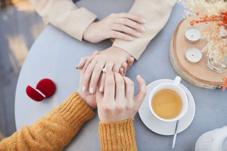 Close-up of man putting a wedding ring on his girlfriends finger at the table during their date in cafe